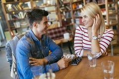 说闲话和聊天在咖啡馆的朋友 库存图片