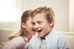 说闲话的兄弟和的姐妹一起谈话和,当在家时坐沙发 免版税库存图片