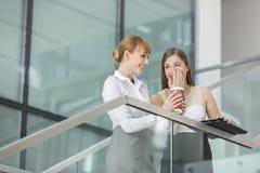 说闲话的女实业家,当食用在步的咖啡在办公室时 库存照片