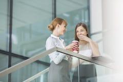 说闲话的女实业家,当食用在步的咖啡在办公室时 图库摄影