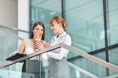 说闲话的女实业家,当食用在步的咖啡在办公室时 免版税库存图片