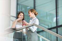 说闲话的女实业家,当食用在步的咖啡在办公室时 免版税库存照片