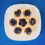 闲谈者平的位置照片用蓝莓和黑莓在蓝色桌上 库存照片