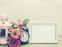 间隔照片框架和蜡烛光和闹钟和人造花背景  库存图片