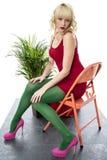 闷热性感的少妇短小套衫连超短裙坐的椅子桃红色高跟鞋 免版税库存照片