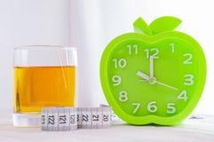 闹钟、一杯汁液和在一张白色木桌上的一卷测量的磁带 r 库存照片