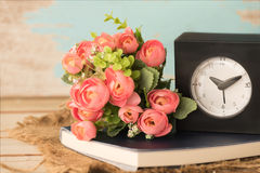 闹钟、人为玫瑰色花笔记本和花束与 免版税图库摄影