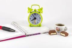 闹钟、开放笔记本和铅笔在白色背景 库存图片