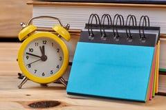 闹钟、螺纹笔记本和堆书 免版税图库摄影