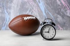 闹钟和橄榄球球 免版税库存图片
