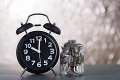 闹钟和步与硬币的硬币堆在w的玻璃瓶子 免版税图库摄影