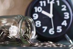 闹钟和步与硬币的硬币堆在w的玻璃瓶子 库存图片