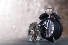 闹钟和步与硬币的硬币堆在w的玻璃瓶子 库存照片