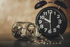 闹钟和步与硬币的硬币堆在w的玻璃瓶子 免版税库存照片