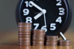 闹钟和步在工作表上的硬币堆,时刻为 免版税库存图片