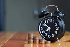 闹钟和步在工作表上的硬币堆,时刻为 免版税图库摄影