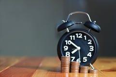 闹钟和步在工作表上的硬币堆,时刻为 图库摄影