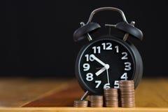 闹钟和步在工作表上的硬币堆,时刻为 库存照片