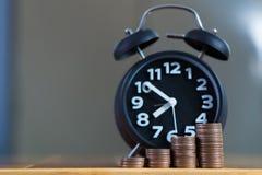 闹钟和步在工作表上的硬币堆,时刻为 库存图片