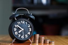 闹钟和步在工作表上的硬币堆,时刻为 免版税库存照片