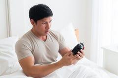 闹钟唤醒的亚裔帅哥在床上在早晨时间 库存图片