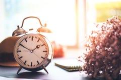 闹钟在地面上 一朵纸、帽子和花在时钟附近 免版税库存图片