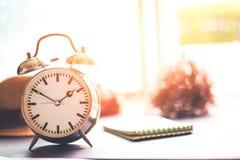 闹钟在地面上 一朵纸、帽子和花在时钟附近 库存照片
