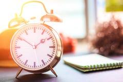 闹钟在地面上 一朵纸、帽子和花在时钟附近 图库摄影