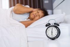 闹钟在早晨和资深妇女关闭醒她的耳朵 库存照片