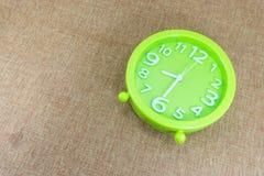 闹钟在棕色麻袋布背景展示半八个o `时钟或8:30 a M 免版税库存图片