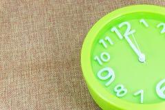 闹钟在棕色麻袋布背景展示12:00 a M 图库摄影