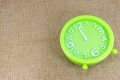 闹钟在棕色麻袋布背景展示12:00 a M 库存照片