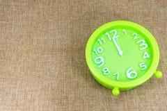 闹钟在棕色麻袋布背景展示12:00 a M 库存图片