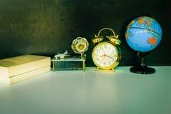 闹钟老葡萄酒金子和地球塑料-预定,在白色的留声机在黑背景 免版税库存图片