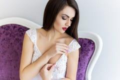 闺房晨衣新娘新娘费的早晨美丽的柔和的女孩与等待在窗口的玫瑰大花束  免版税库存图片
