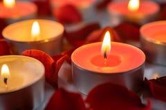 闻的蜡烛有玫瑰花瓣,温暖和舒适背景 库存图片