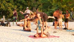 阁帕岸岛,泰国- 2019年2月23日禅宗海滩 年轻人做在沙子的acro瑜伽 力量锻炼户外 集体 股票视频