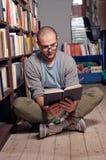 阅读书在图书馆里 免版税库存照片
