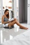 阅读书 享受书家的妇女 休闲,娱乐活动 免版税库存图片