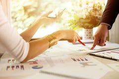 队员谈论数据在会议上 图表和图在表上 业务组象征性人的情形 库存图片