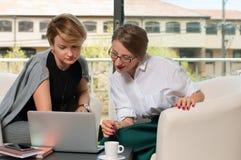 队工作过程 有膝上型计算机的两名妇女在办公室 免版税库存图片