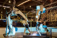 队机器人在汽车工业工厂焊接部分 免版税库存图片