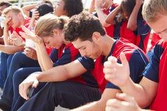队颜色的失望的观众观看体育比赛的 库存图片