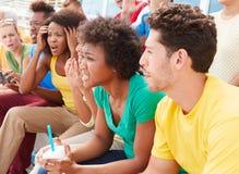 队颜色的失望的观众观看体育比赛的 图库摄影