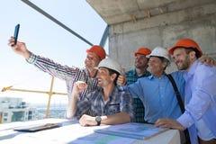 队建造者愉快微笑拍Selfie照片在与建筑师和工程师的会谈期间建造场所的 免版税库存照片
