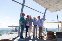 队建造者愉快微笑拍Selfie照片在与建筑师和工程师的会谈期间建造场所的 免版税库存图片