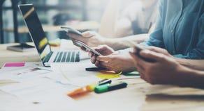 队coworking的过程 照片年轻企业乘员组与新的起始的项目一起使用 在木桌上的笔记本 使用现代 图库摄影