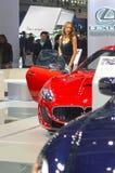 从队Maserati的一个少妇在汽车附近 莫斯科国际汽车沙龙红色和深蓝Maserati 库存照片