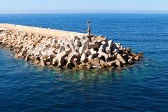 防堤在水晶蓝色海 免版税库存图片