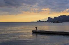 防堤的一位孤立渔夫 免版税库存照片